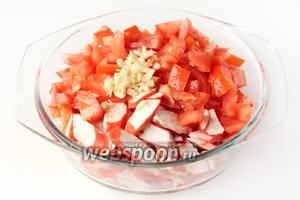 Соединяем подготовленные ингредиенты: крабовые палочки, помидоры и чеснок.