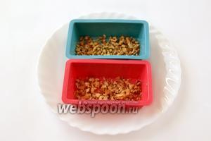 Маленькие силиконовые формочки для кексов или маффинов слегка смазываем маслом (здесь эта процедура нужна), на дно кладём небольшую часть орехов.