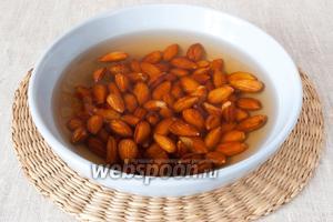 Миндаль залить тёплой водой, чтобы орехи были полностью покрыты водой. Оставить на 2-3 часа, чтобы миндаль разбух.