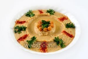 При подаче хумус поливаем арахисовым маслом, посыпаем небольшим количеством паприки и мелко нарезанной зеленью петрушки. Подаем с  питой .