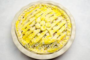 Закрыть пирог решёткой из остатков теста. Смазать сверху желтком. Поставить пирог в горячую духовку. Выпекать в течение 45-50 минут при температуре 180°С.