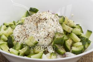 Добавить чистый и нарезанный небольшими ломтиками огурец, заправить салат сметаной. Посолить, приправить. Перемешать.