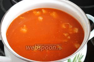 Разогреть процеженный бульон, ввести в него мясо с помидорами и луком.