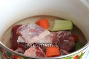 В кастрюлю сложить промытое мясо (у меня хорошие говяжьи рёбра для наваристого бульона — в меру жирные, с большим количеством мяса), крупными кусками нарезанные сельдерей и морковь, четвертинку луковицы.