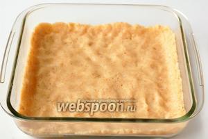 Форму для выпечки размером 15х15 см выложить кулинарной бумагой. Сверху распределить одну часть теста.