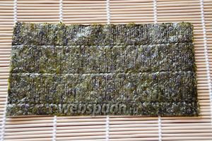 Начинаем делать роллы. Для начала на циновку (нужно обернуть в пищевую плёнку) кладём лист нори, разрезанный пополам.
