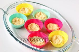 Выложить по 1 столовой ложке теста в смазанные формочки для кексов. В серединке сделать ложкой углубление.