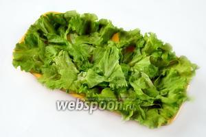 Листья салата промываем, стряхиваем воду и промокаем бумажным полотенцем, рвём листья кусочками и заполняем ими большое плоское блюдо.