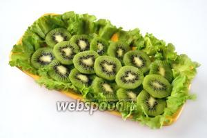 Укладываем на листья салата кружки киви, полностью заполняя блюдо. Оставляем несколько кружков для украшения салата.