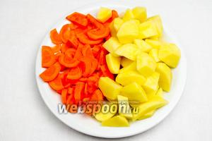 Картофель (3 штуки) и морковь (2 штучки) вымыть, почистить, нарезать картофель кубиком, а морковь полукольцами.