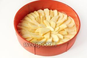 На тесто выкладываем половину яблочных ломтиков, покрывая ими всю поверхность теста.