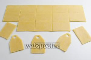 Готовое тесто раскатать. С помощью линейки разделить пласт на прямоугольники 4х6 см. Придать им форму чайного пакетика. Срезать углы сверху, сделать отверстие.