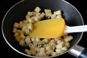 Срезаем корочки с ломтиков батона, нарезаем кубиками, сбрызгиваем оливковым маслом и подрумяниваем на сковороде.