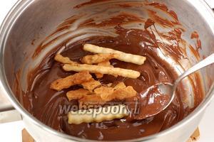 Порциями по 5-6 полосок выкладывать их в шоколад и размешивать ложкой так, чтобы полоски покрылись со всех сторон шоколадом.