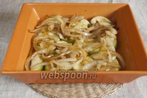 Сверху на яблоки выложить репчатый лук, очищенный, нарезанный полукольцами и обжаренный на оставшемся от мяса жире.