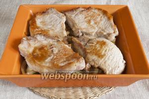 На лук поместить ломтики мяса. Немного посолить, добавить пряности по вкусу, влить в форму вино, закрыть фольгой или крышкой и запекать в духовке 30 минут при 190°C.