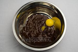По одному втереть в шоколадную массу желтки, тщательно перемешивая.