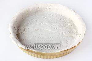Предварительно размороженное слоёное дрожжевое тесто выкладываем в круглую форму диаметром 24 см, формируя бортики. Часто накалываем тесто вилкой.