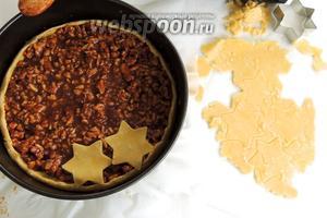 Выложить начинку в форму на тесто. Оставшееся тесто раскатать в пласт и вырезать формочкой звёзды (в оригинальном варианте начинка просто накрывается второй частью теста). Звёзды укладывать плотно друг к другу.