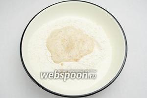 Подошедшие дрожжи залить в лунку муки. Замесить тесто, подливая оставшуюся тёплую воду.