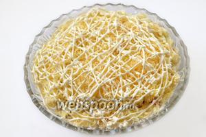 Сыр натираем на тёрке мелкой стружкой, половина сыра — следующий слой, покрытый майонезной сеткой. Далее повторяем все слои, промазывая их майонезом.