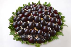 Виноград разрезаем пополам, если есть косточки — удаляем. Укладываем виноград, начиная от середины, по всей поверхности салата. Край салатника декорируем петрушкой, создавая аналог оправы для «драгоценных камней». Салат оставляем в холодильнике не менее чем на час для пропитки.