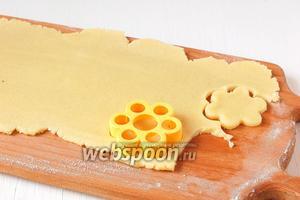 Раскатать тесто на подпылённой мукой доске толщиной 0,4 см. Вырезать с помощью формочки заготовки для цветов.
