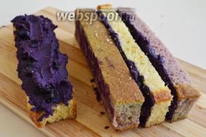 Смазывайте черничным ганашем стороны бисквитных брусков разного цвета и соединяйте их вместе. В ганаш равномерно всаживайте оставшиеся ягоды черники для сборки торта.