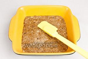Взять форму и выложить орехово-овсяную смесь, аккуратно разровнять слой лопаткой (оставить 2 ст. л смеси для украшения).