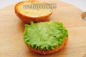 Промойте и обсушите бумажным полотенцем листья салата и разложите их на нижние части булочек.