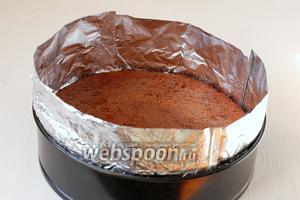 Бисквит поместить в форму, в которой он выпекался, фольгой наростить бортики. Сбрызнуть бисквит 2-3 столовыми ложками коньяка. Поместить бисквит в форме в морозильник.