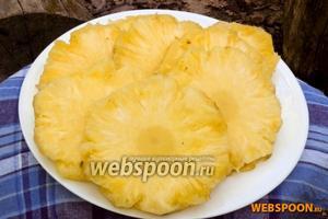 Срезать донышко у ананаса, поставить его вертикально, срезать бока. Держась за макушку нарезать мякоть шайбами толщиной около 1,5 см.