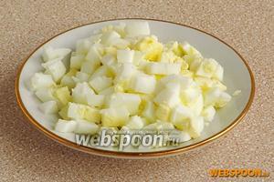 Яйца отварить вкрутую, очистить и нарезать кубиками.