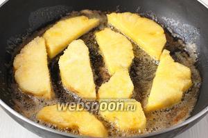 В сковороде растопить сливочное масло и обжарить в нём ананас в сахаре по 4-5 минут с каждой стороны до карамелизации ананаса.