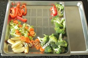 Овощи выкладываем на противень с отверстиями. И под него устанавливаем поддон без отверстий.