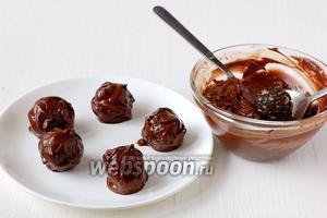 С помощью двух ложек покрыть каждую конфету растопленным шоколадом.