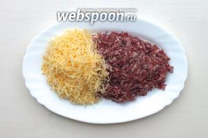 Мелко натрите на тёрке сыр. Нарежьте маленькими кусочками колбасу.