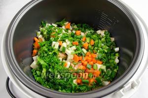Добавить в чашу нарезанную зелень, чеснок и морковь.