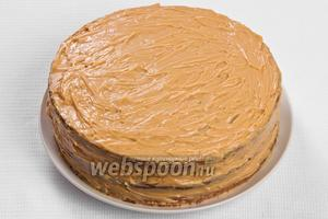 После того, как на смазанный второй корж положили третий, его вместе с боковымы поверхностями торта обмазываем кремом.