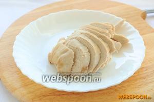 Остывшее куриное филе нарезать на ломтики.