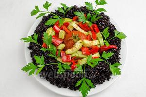 Выложить овощи внутрь кольца из риса. Украсить зеленью. Взбрызнуть овощи оливковым маслом. Посолить. Поперчить. Блюдо готово. Его можно подавать к обеду, ужину.