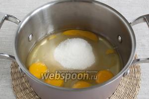 В небольшую кастрюлю с толстым дном поместить яйца, добавить сахар.