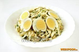 Перемешиваем пекинскую капусту с соусом, выкладываем горкой в центр широкого салатника или тарелки. По верху кладём кружки варёного яйца.