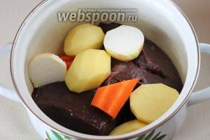Все продукты, кроме чеснока, нарезать крупными кусками и уложить в кастрюлю.