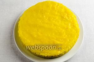 Смазать заварным кремом с помощью силиконовой кулинарной лопатки верхнюю поверхность части коржа. Сверху выложить вторую часть, третью и тоже смазать заварным кремом. Затем смазать кремом бока торта.