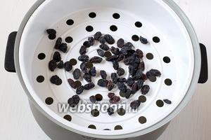 Сверху в чашу выложить ёмкость для приготовления на пару. В ёмкость выложить промытый изюм.