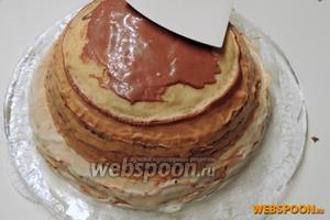 Затем кладём самые малые блины. Половину от шоколадного крема с творогом распределяем сверху каждого блина. Обмазываем и бока торта.