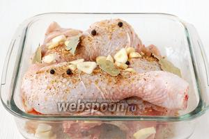 Чеснок порезать пластинками. Пересыпать части курицы лавровым листом, перцем горошком, пластинками чеснока.