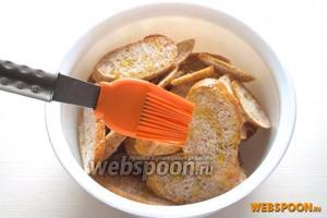 Аккуратно (каплями) распределите оливковое масло по ломтикам багета с помощью кисточки. Не нужно лить много масла, иначе в процессе приготовления оно начнёт гореть. Масло в данном рецепте используется исключительно для придания сухарикам вкуса и аромата.