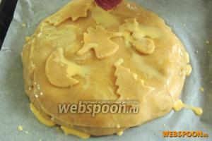 Из оставшихся обрезков теста выдавим фигурки. Выкладываем их сверху. Затем возьмём желток с ложкой молока и обильно смажем весь пирог.